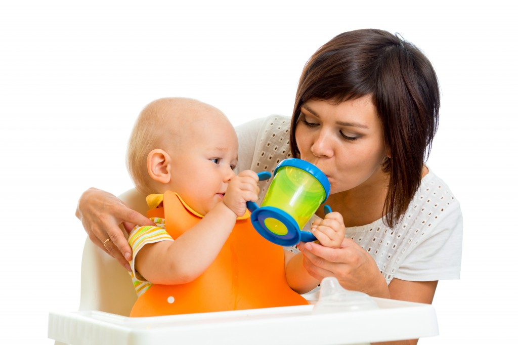 woman and baby drinking from sippy cup